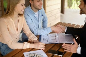 Real estate agent and clients shaking hands after signing property agreement